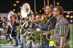Bob Jender, Matt's father, stands at the end of the line of alumni band members during Friday's halftime performance.