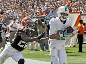 Miami Dolphins wide receiver Brian Hartline, right, catches a 34-yard touchdown pass against Cleveland Browns cornerback Buster Skrine.