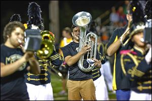 Matt Jender of Perrysburg plays his baritone during the half time performance of the Perrysburg alumni marching band.