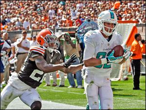 Miami's Brian Hartline, a former Ohio State receiver, catches a 34-yard touchdown pass against Cleveland's Buster Skrine in the third quarter.