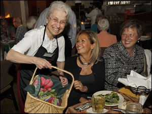 Sister Ann Carmen Barone gives M&Ms to Renee Huebner and Jill Trosin during celebrity night for Lourdes University.
