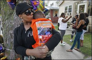 Franshawn Harris kisses her grandson, James Bragg III, outside his house on Cottage Street in Toledo. James lost his dad, James Bragg, to a shooting over the weekend.