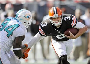 Browns quarterback Brandon Weeden is sacked by Miami's Randy Starks in the fourth quarter. Weeden was sacked six times and hammered repeatedly after several other throws.