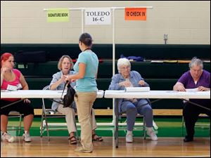 Jessica Flores checks in to vote at the polling place inside Beverly Elementary School in Toledo. Poll workers, from left, are Megan Marion, Carolyn Davis, Sharon Hickey, and Mary Skibski.  The Blade/Dave Zapotosky