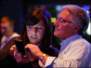 Mayor Mike Bell supporters Jennifer Sorgenfrei and Mark Luetke look at election returns.