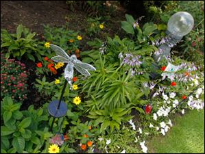 Marie likes to mix garden art into the design of her flower beds.
