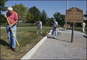 From left: Volunteers Ben Driver of Maumee,  Carl Battig of Holland, and Doug Towslee of Maumee, facing left,  work on the walkway honoring Masons who served in the War of 1812 at Fort Meigs.