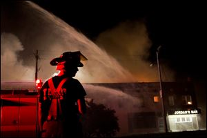 Members of the Toledo Fire Department battle a fire at the corner of Front and Euclid September 10, 2013 in East Toledo.