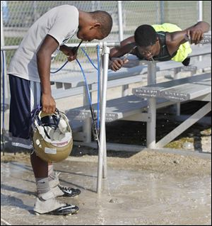 Dink Wyatt, left, and C.J. Chilupe take a water break during football practice at Maumee High School.