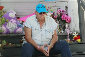 Terry Steinfurth, Sr., Elaina Steinfurth's grandfather, sits outside the Federal Street home where she went missing and where her remains were found three months later in a detached garage after numerous searches by police and family.