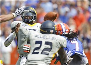 Toledo quarterback Terrance Owens, left, throws a pass under pressure.