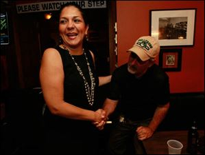 Anita Lopez shakes hands with Councilman Steven C. Steel on election night at Michael's Bar & Grill.