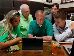 From left: Elizabeth Bolduc, Bob Reinbolt, D. Michael Collins, and campaign managers Steve Leggett and Christopher Fofrich search for primary election results during his campaign party at Doc Watson's in Toledo, Ohio.