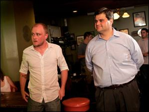 Joe McNamara watches along with campaign volunteer Evan Watkins of Toledo as results are announced on television.