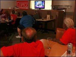 Lopez supporters watch candidates during live television coverage of the elections from Michael's Bar & Grill on September 10, 2013. Ms. Lopez had not yet appeared to thank her campaign workers and supporters.