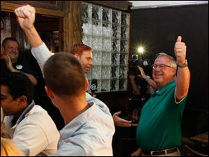 Deputy campaign manager Christopher Fofrich, left, and D. Michael Collins react to Collins taking second in the primary election during his campaign party at Doc Watson's in Toledo, Ohio.