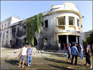 People gather to look at the site of a car bombing in Benghazi, Libya.