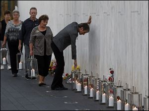 Secretary of the Interior Sally Jewell, center, pauses as she places a lantern at the wall containing the 40 names of the crew and passengers of Flight 93 at the Flight 93 National Memorial on Tuesday.
