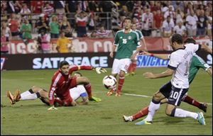 United States' Landon Donovan, right, scores a goal as Mexico goalkeeper Jose de Jesus Corona watches during the second half of a World Cup qualifying soccer match Tuesday in Columbus.