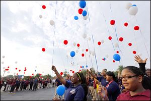 "Senior Toni Payton, right, joins schoolmates in re-leasing a balloon during a ""We Have Not Forgotten"" tribute at Horizon Science Academy Toledo."