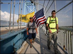 Army veterans Brian Stark, left, and Michael Lattea, right, cross over the Maumee River on the High Level Bridge.