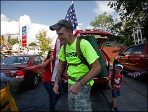 Iraq veteran Michael Lattea, center, has the American flag he is caring straightened out by veteran Nicole Willoughby, center left, as her son Tim, 6, right, and fellow veteran Brian Stark, left, get ready to continue their walk through East Toledo after a water break  off Woodville Road.