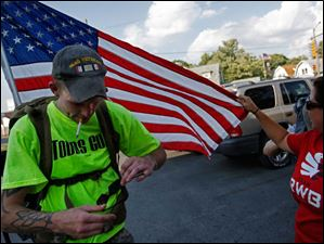 Iraq veteran Michael Lattea, left, has the American flag he is caring straightened out by fellow veteran Nicole Willoughby, right, as her son Tim, 6, not pictured, and fellow veteran Brian Stark, also not pictured, get ready to continue their walk through East Toledo after a water break  off Woodville Road.