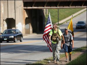 Michael Lattea, left, and Brian Stark walk along Woodville Road in East Toledo.