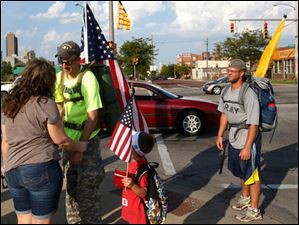 Tim Willoughby, 6, center, and veteran Brian Stark, right, pause in their walk as Iraq veteran Michael Lattea, center left, hugs veteran's supporter Jewel Baker, of Perrysburg, left, during the group's walk through East Toledo