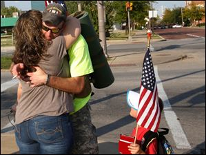 Tim Willoughby, 6, right, pauses in his walk as Iraq veteran Michael Lattea, center, hugs veteran's supporter Jewel Baker, of Perrysburg, left, as the pair and fellow veteran Brian Stark walk through East Toledo