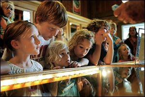 From left, Rosie Kelly, 6, Clyde Kelly, 10, Penny Kelly, 5, and Aubrey Wilhelm, 6, watch the marble-making demonstration. The children were visiting from Spring Lake, Mich.