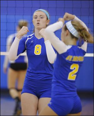 St. Ursula Academy players Lauran Graves (8) and Madelyn McCabe (2) celebrate a point.