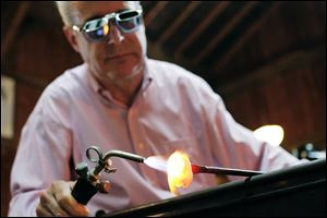 Glass artist Mark Matthews of Wauseon uses a blowtorch help shape a blob of molten glass that will become a marble during a demonstration at Sauder Village in Archbold, Ohio.
