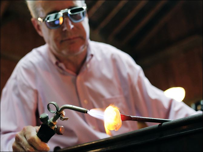 0001010100000600000 Glass artist Mark Matthews of Wauseon uses a blowtorch help shape a blob of molten glass that will become a marble during a demonstration at Sauder Village in Archbold, Ohio.