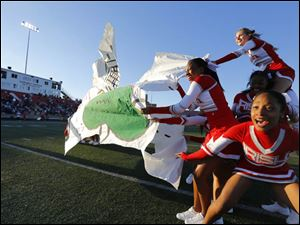 Central Catholic cheerleaders panic as their sign tears in the wind before the team takes the field.