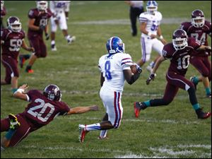 Springfield senior Terrance Cole (8) dodges a large group of Rossford players after i
