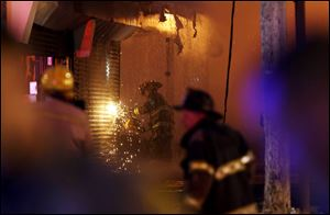 A firefighter saws through a metal wall on a building while battling a fire at the Seaside Park boardwalk on Thursday in Seaside Park, N.J. The fire began in a frozen custard stand on the Seaside Park section of the boardwalk and quickly spread north into neighboring Seaside Heights.