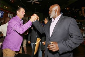 Mayor Mike Bell is greeted by Steve Cady at an election night party at Mulvaney's Bunker Irish Pub in Toledo. Defeating Mr. Bell in the November election is the Democratic Party's top goal.