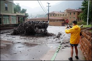 John Shada, of Manitou Springs, Colo., takes a photo of flood water as it shoots out of a sewer on Canon Avenue on Thursday in Manitou Springs, Colo.