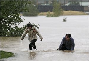 A couple plays in flood water at Utah Park in Aurora, Colo., on Thursday. The park was under water due to flooding.