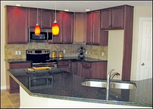 The efficient kitchen includes a stainless stove and built-in microwave, as well as a dishwasher.