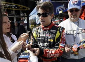 Driver Jeff Gordon signs autographs for fans as he walks to his garage today during practice for Sunday's NASCAR Sprint Cup Series auto race at Chicagoland Speedway in Joliet, Ill.