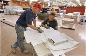 Electricians Jason Pietrowski, left, and Scott Koelsch look over blueprints for installing kitchen equipment in the new Kroger in Maumee. Kroger also plans a new Marketplace store next year on Airport Highway at Holloway Road.
