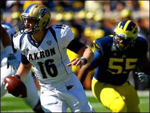 Akron sophomore quarterback Kyle Pohl (16) looks to pass as Michigan senior Jibreel Black (55) runs to attempt a tackle.