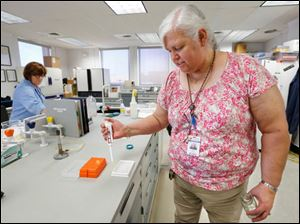 Chief chemist Brenda Snyder demonstrates the test for microcystis at the Collins Park Water Treatment Plant.
