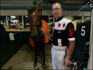 Driver Mark Headworth stands next to the horse Monstro Hanover, who he ran in the first race.