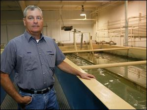 Henry Biggert, plant superintendent, next to one of the trains through which the water is filtered.