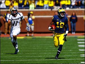 Michigan junior Blake Countess (18) runs the ball after intercepting an Akron pass.