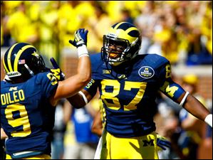 Michigan players sophomore Devin Funchess (87) and senior Drew Dileo (9) celebrate.