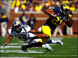 Michigan senior Jeremy Gallon (21) dodges Akron senior Malachi Freeman (20).